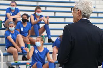 University President Fred P. Pestello speaks to members of the women's soccer in Robert R. Hermann Stadium.