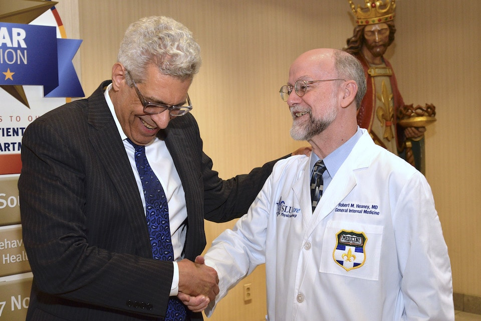 University President Fred P. Pestello, Ph.D., shakes hands with Robert Heany, M.D., SLUCare's chief medical officer. Photo by Kevin Lowder