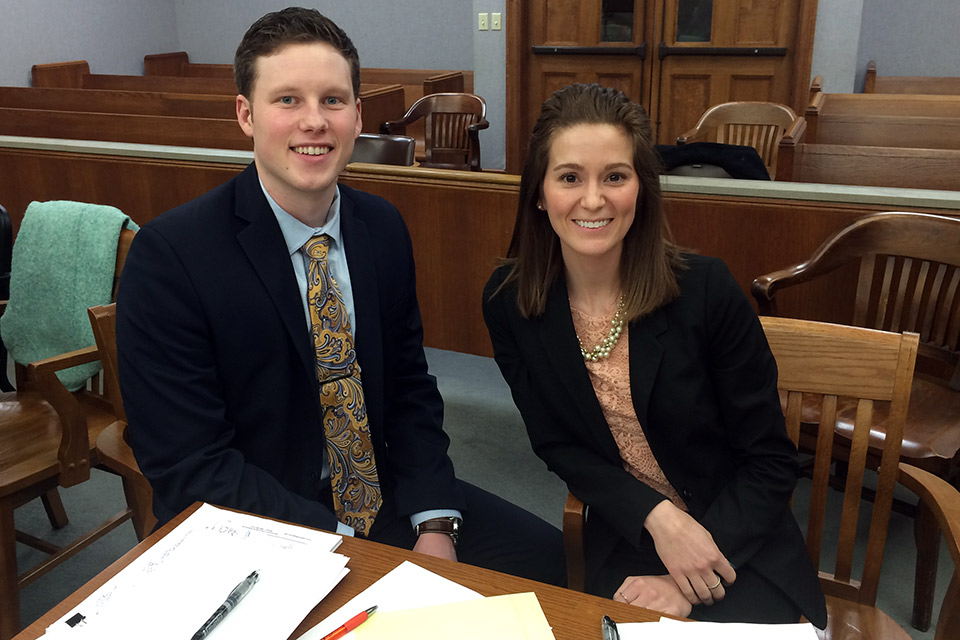 Ryan Reed and Emily Bell in courtroom