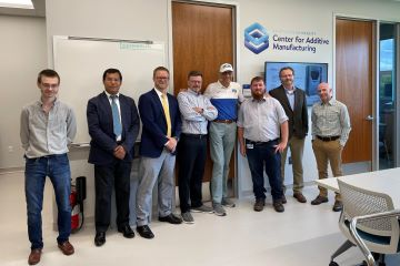 University President Fred P. Pestello, Ph.D., toured the new Center for Additive Manufacturing at Saint Louis University. Pestello (center) is pictured with from l-to-r: Michael Borovik, Vasit Sagan, Ken Olliff, Andrew Hall, Andre Castiaux, Scott Martin and Scott Sell. Photo by Carrie Bebermeyer.
