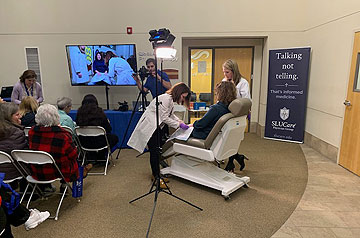 SLUCare Physicians demonstrate a dermatological technique (seated and standing figures at right) at an outreach event.