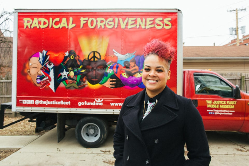 Amber Johnson, Ph.D., stands in front of a Justice Fleet bus.