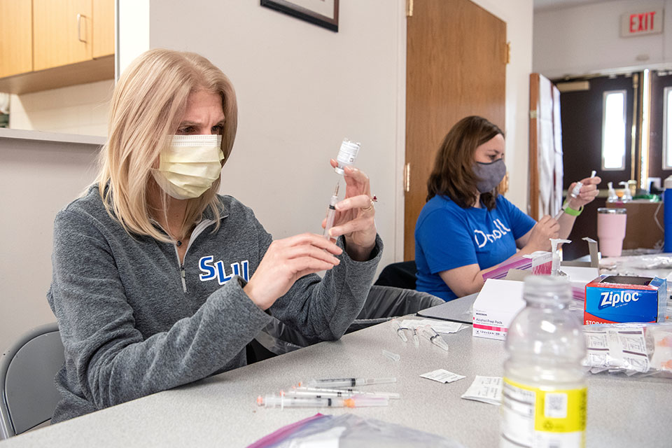 Professors Terri Rebmann and Deborah Horton prepare vaccine doses during a vaccination clinic that SLU held in March at Beloved Community United Methodist Church. The pair were among key leaders who guided the University's response to COVID-19.