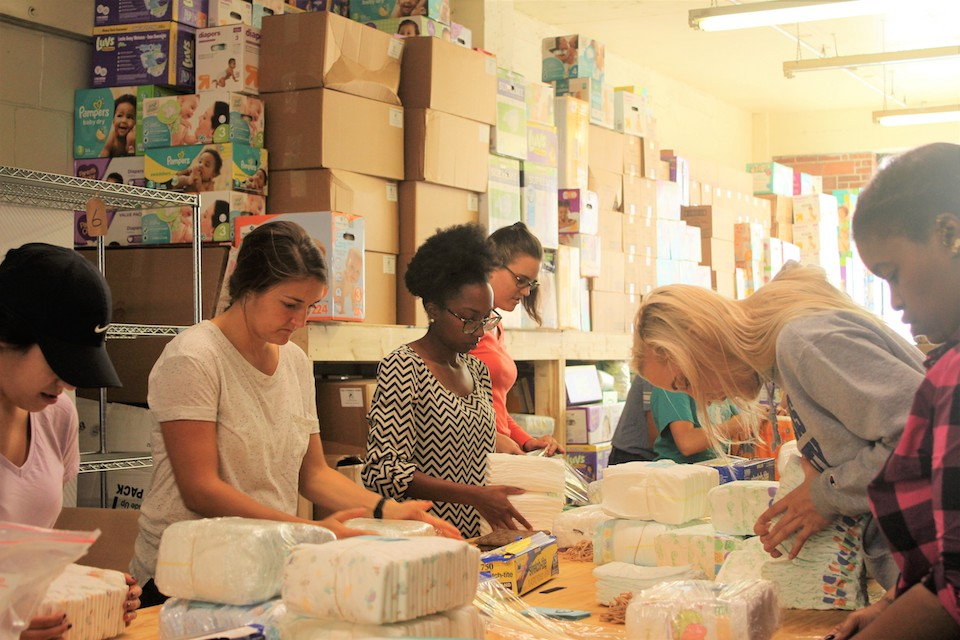 Students organize diapers into packets to be distributed in the St. Louis region.