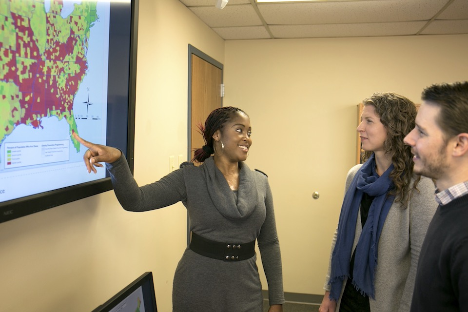 Asabe Garba, a Master of Public Health student, points to a map of obesity rates in the United States. Her professor, Katie Stamakakis, look on from right.